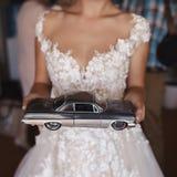 La jeune mariée tient un rétro modèle de voiture dans des ses mains Photos stock
