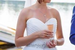 La jeune mariée tient un verre de champagne Photo stock
