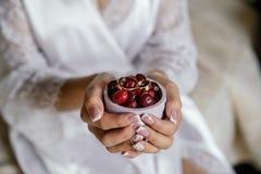 La jeune mariée tient une tasse avec un cornouiller et des anneaux de mariage Photos stock