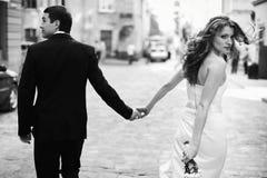 La jeune mariée tourne tenir autour la main du marié tout en marchant autour du Photo libre de droits