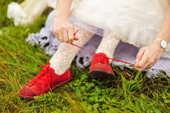 La jeune mariée utilise les espadrilles rouges Photographie stock libre de droits