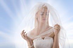 La jeune mariée avec le voile sur le visage regarde la gauche Photographie stock