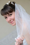 La jeune mariée couverte de voile regarde loin Images stock