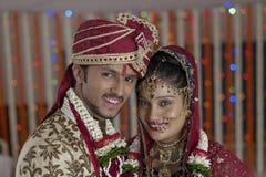 La jeune mariée indoue indienne et toilettent un couple de sourire heureux. Image libre de droits