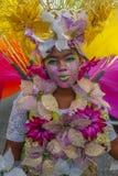 La jeune mascarade femelle sourit avec une timidité feinte dessus pendant un défilé de carnaval dans St James Trinidad Photographie stock libre de droits