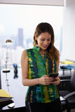 La jeune messagerie textuelle de femme de Latina au téléphone dans le bureau Photos stock