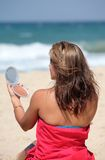 La jeune mise bronzée de femme composent en fonction tandis que sur la plage photos stock
