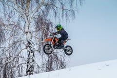 La jeune moto de coureur de moto vole après avoir sauté par-dessus la montagne Photo stock
