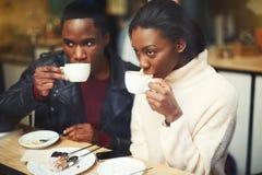 La jeune obscurité a pelé le café potable d'homme et de femme tout en se reposant ensemble en café moderne dans le jour d'hiver f Image libre de droits