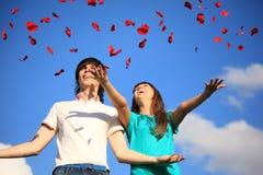 La jeune paire disperse des pétales des roses contre le ciel Image libre de droits