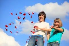 La jeune paire disperse des pétales des roses contre le ciel Image stock