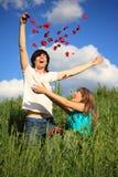 La jeune paire disperse des pétales des roses dans l'herbe Photographie stock