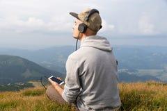 La jeune personne masculine apprécie la musique dans le casque du téléphone portable en montagnes Photographie stock libre de droits