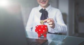 La jeune pièce de monnaie d'ondulation de baisse de femme d'affaires dans le rouge a pointillé la tirelire Photos libres de droits