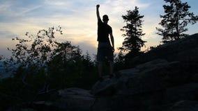 La jeune position, célèbrent sur la roche en pierre dans le paysage tchèque avec des arbres au coucher du soleil banque de vidéos