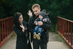 La jeune promenade de famille et de fils le long du lac étayent Image libre de droits