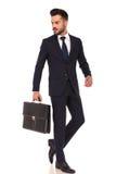 La jeune serviette de transport d'homme d'affaires marche et regarde en arrière Images stock