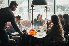 La jeune société a l'amusement et mange dans la barre tabagisme d'un narguilé, communiquant dans un restaurant oriental Images stock