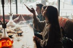 La jeune société a l'amusement et mange dans la barre tabagisme d'un narguilé, communiquant dans un restaurant oriental Photos stock