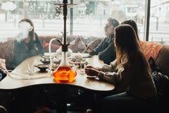 La jeune société a l'amusement et mange dans la barre tabagisme d'un narguilé, communiquant dans un restaurant oriental Photographie stock libre de droits