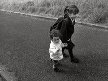 La jeune soeur marche avec sa soeur plus âgée à l'école Images stock