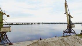 La jeune, sportive femme faisant des exercices, s'accroupit, sur le dessus arénacé de la carrière, sur la plage Sur le fond peut  clips vidéos
