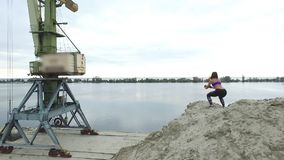 La jeune, sportive femme faisant des exercices, s'accroupit, sur le dessus arénacé de la carrière, sur la plage Sur le fond peut  banque de vidéos