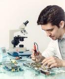 La jeune technologie masculine énergique ou l'ingénieur répare l'equipme électronique Photos libres de droits