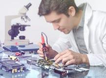La jeune technologie masculine énergique ou l'ingénieur répare l'equipme électronique Image libre de droits