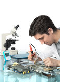 La jeune technologie masculine énergique ou l'ingénieur répare l'equipme électronique Photographie stock