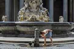 La jeune touriste avec du charme de fille boit l'eau d'un poste d'eau potable antique du nez romain dans la perspective d'histori photos stock