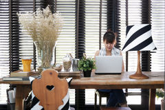 La jeune travailleuse active asiatique utilise un ordinateur portable Photo stock