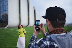 La jeunes femme et homme de couples font la photo au téléphone portable à Bakou Homme et femme modernes de hippie à l'aide du tél photographie stock libre de droits