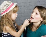 La jeunes mère et fille de famille composent au miroir Images libres de droits
