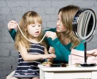 La jeunes mère et fille de famille composent au miroir Image libre de droits