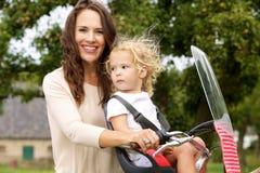 La jeunes mère et fille sur la bicyclette montent en parc Images libres de droits