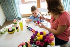 La jeunes mère et fils heureux peignent des oeufs de pâques image libre de droits
