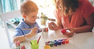 La jeunes mère et fils heureux peignent des oeufs de pâques photographie stock