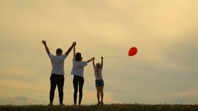 La jeunes mère et père avec la fille sont riants et jouants avec le ballon sur le pré au fond de coucher du soleil Aimer heureux banque de vidéos