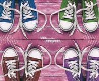 La jeunesse a coloré des espadrilles sur la vieille surface en bois rose, vue supérieure Image libre de droits