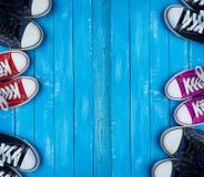 La jeunesse a coloré des espadrilles sur un fond bleu des planches en bois Photo stock