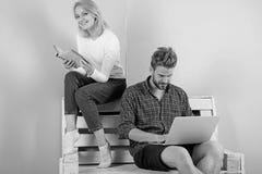 La jeunesse dépensent des loisirs recherchant l'information Couplez les étudiants avec le livre et l'ordinateur portable recherch image libre de droits