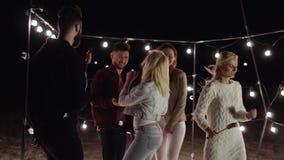 La jeunesse danse avec des saucisses sur des brochettes dans des mains à la plage de soirée sur le fond du décor avec des lampes banque de vidéos
