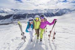 La jeunesse heureuse dans les alpes colorées de ski de vestes recourent Images libres de droits