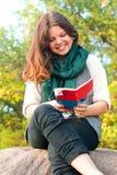 La jolie écolière lit la brochure en parc d'automne Images stock