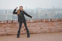 La jolie adolescente avec des écouteurs a plaisir à écouter la musique du smartphone et de la danse dehors image stock