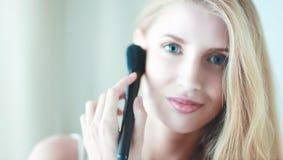 La jolie application de femme composent avec la brosse Photos stock