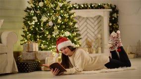 La jolie brune avec des histoires de Santa Hat Reading Some Funny s'étendant sur le plancher dans Noël a décoré à la maison Madam banque de vidéos