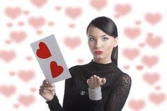 La jolie brune avec la carte postale de valentine envoient un baiser Photo libre de droits