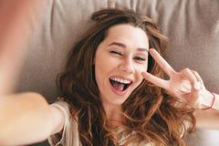 La jolie dame émotive étonnante font le selfie faire le geste de paix photographie stock